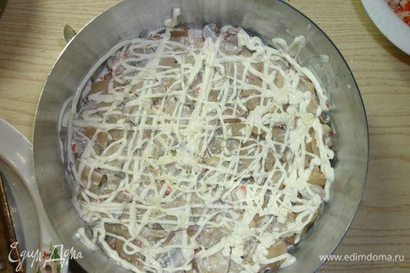 Третьим слоем укладываю грибы. У меня грибы резанные, поэтому дополнительной нарезки не требуют. Также делаю сетку из майонеза.