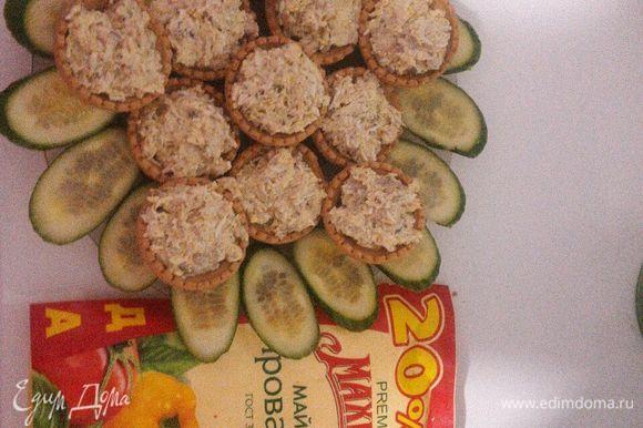 Выложить получившуюся смесь в тарталетки, украсить огурчиком свежим.