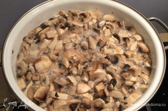 За это время приготовить начинку. Грибы вымыть, нарезать кубиком. В большой кастрюле вскипятить воду, посолить воду, добавить нарезанные грибы и отварить их около минуты. Откинуть грибы в дуршлаг, дать воде стечь.