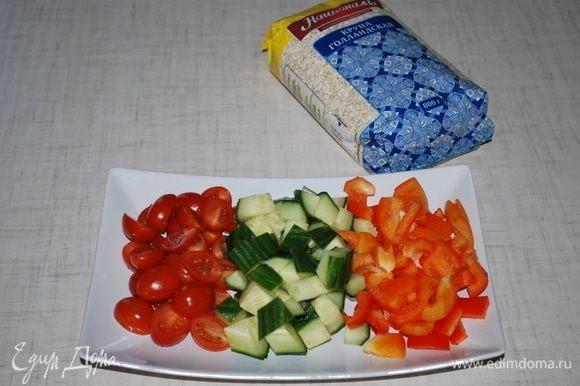 Помидоры черри разрезать на две части, огурец и болгарский перец порезать кубиками.