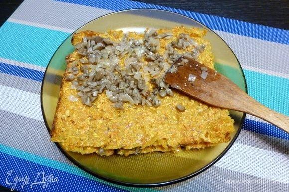 Разрезать большой корж на 4 части. Прокладывать каждый корж начинкой из соленых груздей.