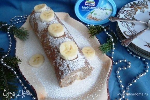Рулет развернуть, намазать кремом и свернуть обратно. Завернуть в фольгу или пленку и убрать в холодильник на 30 минут. Но чем дольше он там пробудет, тем лучше пропитается. Рулет присыпать сахарной пудрой и украсить кружочками банана. Приятных Вам праздников!
