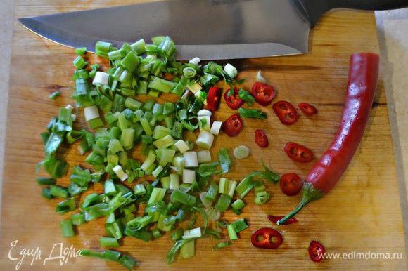Зеленый лук и перец чили нарезать тонкими ломтиками.