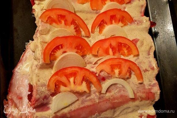 Перед тем, как отправить ребра в духовку, делаем небольшие надрезы и укладываем туда помидоры и лук, нарезанные полукольцами.