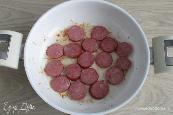 После ребер обжарьте кусочки колбасы и тоже уберите их на время.