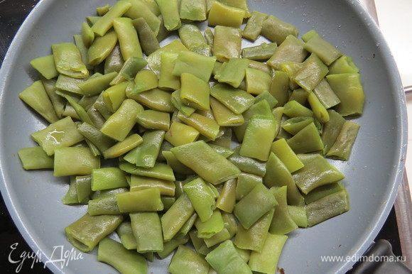 Зеленую фасоль обжарить на сковороде на оливковом масле, добавить чеснок. Вареную морковь нарезать кубиками.