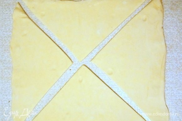 Слоеное тесто разморозить и раскатать не очень сильно. Разрезать по диагонали на четыре треугольника.