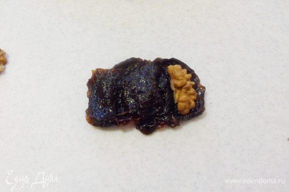 Каждую ягоду чернослива надрезать вдоль, вложить четвертинку грецкого ореха.