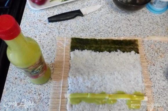 Выложить на шершавую поверхность нори рис, оставив 1–2 см листа не покрытым. Выложить бруски феты, полить соусом васаби.