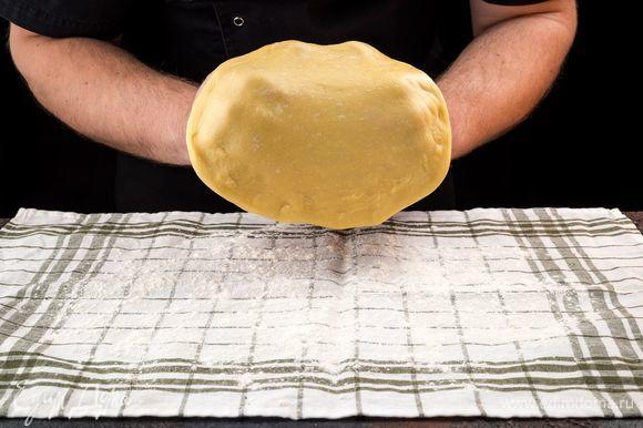 Большое хлопчатобумажное полотенце присыпьте мукой, раскатайте на нем тесто как можно тоньше.