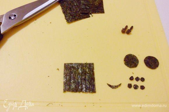 Из листа водорослей нори ножницами вырезать «улыбку» медвежонка и кружочки разного размера для лапок «ножек».