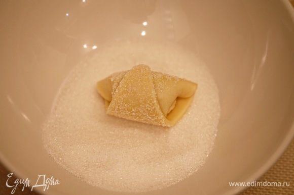Сахар пересыпать в глубокую тарелку. Обмакнуть каждый рогалик в сахарном песке.