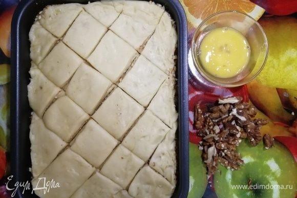 Наметьте тесто на порционные заготовки. Яйцо взбейте. Грецкие орехи разрежьте на 2 части.