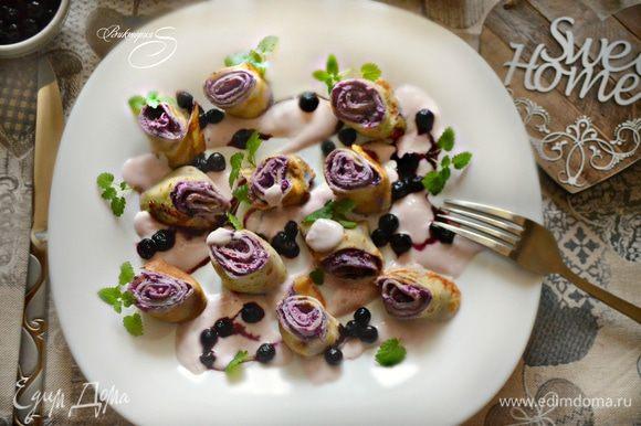 Для подачи рулетики нарежьте кусочками шириной 2 см. Выложите на тарелку и полейте приготовленным соусом, украсьте ягодами и мятой.