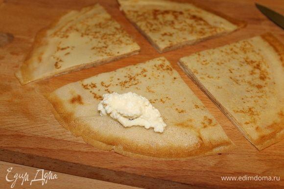 Творог протрите через сито, добавьте сахар, ванилин и распаренный изюм, который лучше нарезать маленькими кусочками. Берите сразу несколько испеченных блинчиков, разрежьте на 4 части и на каждую четвертинку положите по 1 ч. л. начинки. Начинка может быть любая — мясная, грибная, но сегодня будет творог.