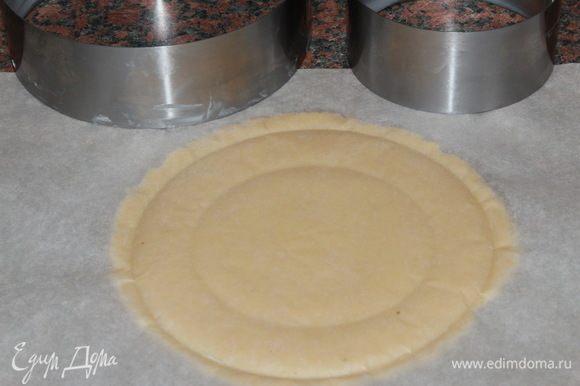 Тем временем тесто охладилось и с ним можно работать. Работать придется быстро: помним, что песочное тесто нельзя перегревать. Поэтому, если оно сильно размягчилось, отправьте его на некоторое время в морозильную камеру. А потом снова продолжайте работать. Я готовила несколько тартов разного диаметра. У меня было два тарта по 16 см, один тарт 18 см, два тарта 10 см. Как раз на все это использовала все тесто. Отрезаем кусок теста, выкладываем его между двумя листами пергамента и раскатываем в круг толщиной 3 мм. Почаще, при раскатке, переворачивайте тесто в пергаменте, чтобы равномерно раскатать и не дать ему быстро нагреться. Каждый раз, когда переворачиваете, отрывайте пергамент от теста. Таким образом вы никогда не пропустите то время, когда тесто критично нагрелось: пергамент начнет рвать тесто. Затем намечаем кольцом размер будущего тарта: осторожно надавливаем (не продавливаем) через пергамент кольцом, размер которого соответствует диаметру будущего тарта и потом кольцом, диаметр которого на 2 см больше. Потому как бортики будут высотой 2 см. Затем снимаем верхний пергамент, обрезаем излишки теста, быстро переворачиваем тесто, снимаем второй пергамент и опускаем тесто в кольцо. Внутреннюю стенку кольца предварительно смазываем маслом.