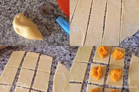 Спустя 30 минут посыпать рабочую поверхность мукой, отрезать небольшой кусочек теста и тонко раскатать. Затем вырезать меленькие квадратики и разложить на них небольшое количество начинки.