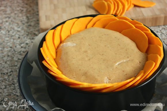 Вынуть чизкейк из духовки. Воткнуть в начинку ломтики тыквы вертикально внахлест (примерно на половину ломтика), начиная с периферии.