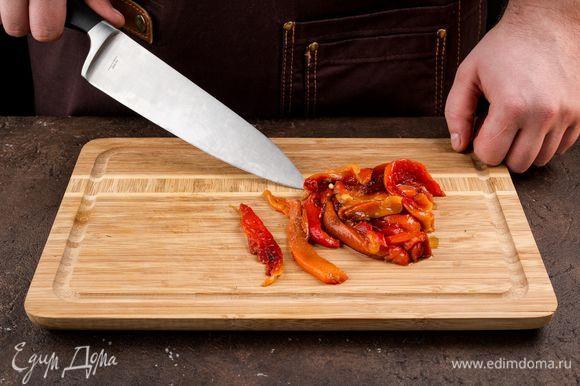 Болгарский перец запеките в духовке, снимите кожицу и нарежьте полосками.