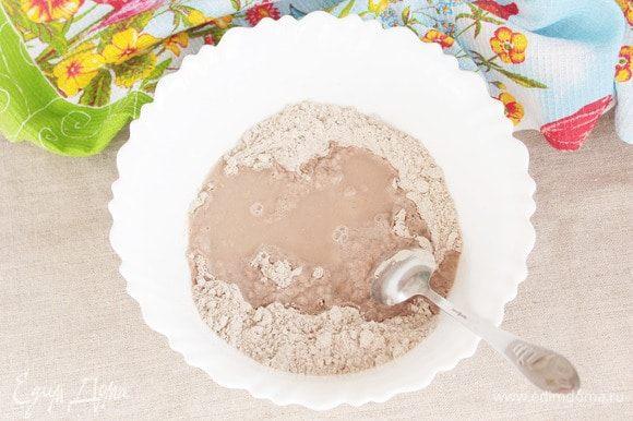 Влить в мучную смесь фруктовый сироп (4 ст. л.) и небольшое количество воды. Начать замешивать тесто.