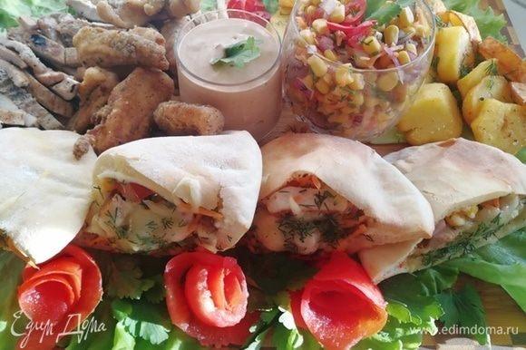 На доску я выкладываю питы, оставшийся салат, острый соус из майонеза, соуса чили и терияки, картофель, поджаренный кружочками, стрипсы куриные и нарезанный стейк.