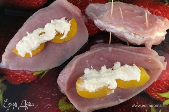 Разрезать куриные грудки так, чтобы образовался кармашек. В него кладем половинки персиков и сырную начинку. Скрепляем зубочистками. Выкладываем в форму, смазанную маслом, грудки и картофель, нарезанный пополам. Запекаем в духовке 40 минут при температуре 180°С.