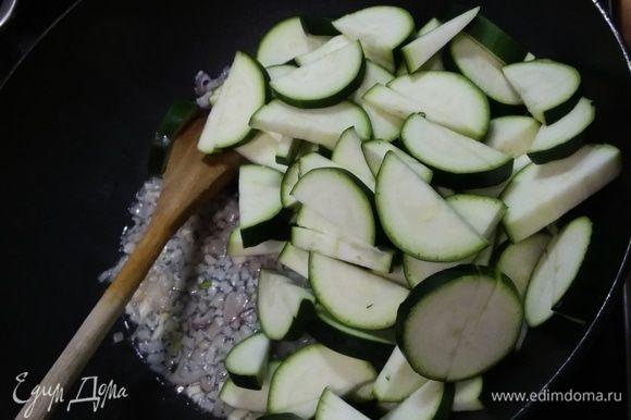 В глубокой сковороде разогреть масло и пассеровать лук (подойдет и репчатый) и чеснок. Добавить цукини, нарезанные на полудольки. Обжарить в течение нескольких минут. Поставить вариться рис.