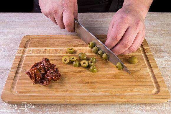 Нарежьте вяленые томаты и оливки пополам.