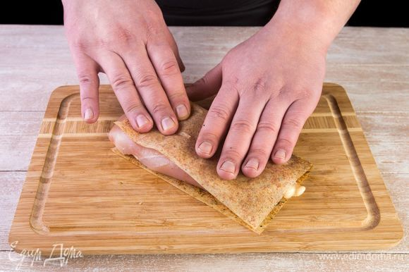 Положите отбитое филе на половину листа MAGGI®, закройте второй половиной и прижмите рукой.