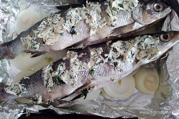 Духовку разогреть до 200°С. Рыбу обсушить салфетками. Надрезы и брюшко заполнить ароматным маслом. На фольгу, смазанную растительным маслом, поместить нарезанный кольцами лук, сверху уложить рыбку.