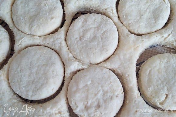 Руками распределить тесто в пласт толщиной около 2 см. Можно раскатать скалкой. Формочкой вырезать булочки. Оставшееся тесто снова собрать в комок и вырезать еще несколько штук. Получается около 12 булочек. Смазать верх булочек молоком и посыпать тертым сыром.