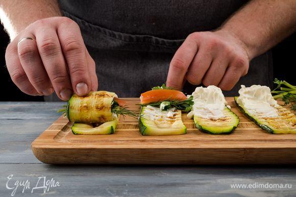 На каждую полоску цукини нанесите с одной стороны сырную смесь. На один край положите полоску помидора и немного зелени. Аккуратно заверните рулетик.
