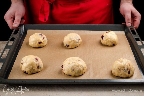 Оставьте тесто на час, накрыв его салфеткой. Сформируйте колобки и выложите их на противень, покрытый пергаментом, оставив на 20 минут для расстойки.