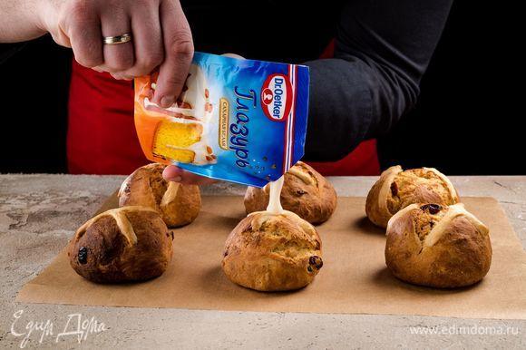 Срежьте уголок пакетика и украсьте глазурью остывшие булочки.