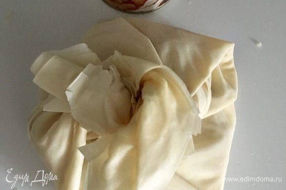 Теперь листы фило сворачиваем в виде мешочка с сыром внутри. Кончики можно сколоть зубочисткой для прочности и верности. Переносим мешочек на противень, выстеленный пергаментом.