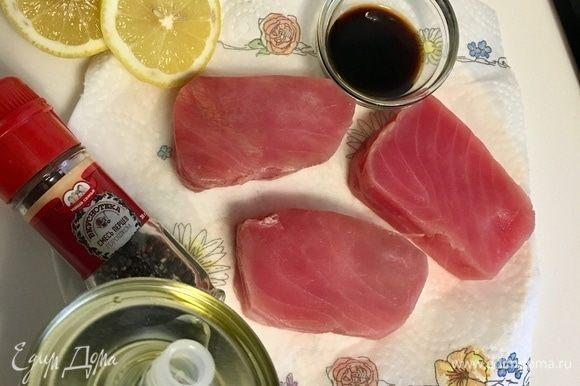 Сначала займемся тунцом. У меня были уже готовые замороженные стейки. Разморозить, помыть, обсушить бумажным полотенцем. После этого сбрызнуть каждый кусочек оливковым маслом, лимонным соком, соевым соусом, поперчить по вкусу. Солить не надо. Соевого соуса и так достаточно. Лучше подать его потом отдельно к готовой рыбе.