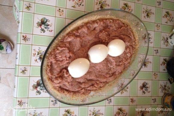 В жаропрочную форму выложить половину фарша и отварные яйца, накрыть второй половиной фарша.