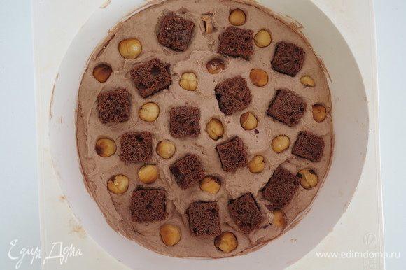 Равномерно распределить кубики шоколадного бисквита и обжаренный фундук, вдавливая их в ганаш, заморозить в морозилке до твердого состояния для удобства сборки.