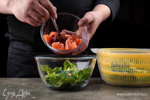 Выложите грейпфрут и свеклу на листья салата. Выжмите сверху оставшийся сок из грейпфрута.