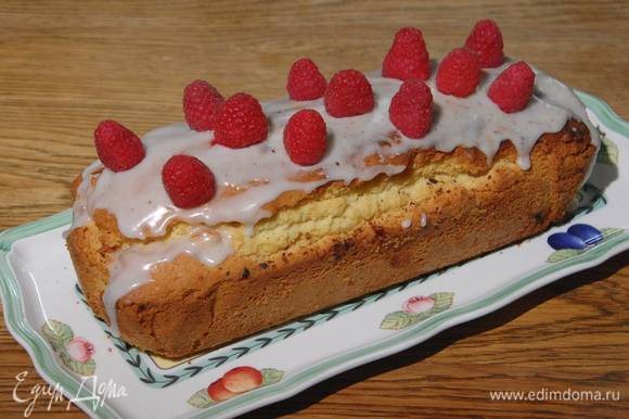 Готовый теплый кекс покрыть сахарной глазурью и украсить свежей малиной.