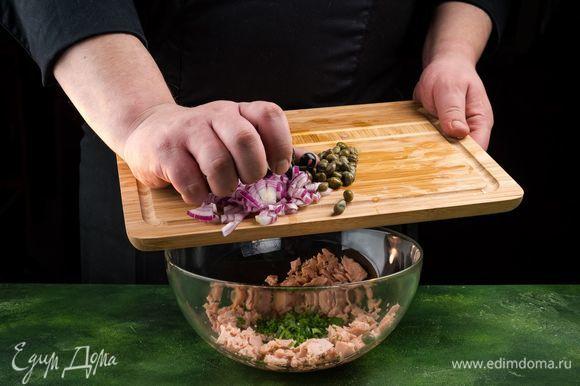 Добавьте к тунцу лук, петрушку, маслины и каперсы. Все перемешайте.