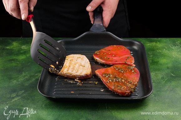 По истечении времени уберите с рыбы лишний маринад и обжарьте филе тунца на сковороде-гриль с одной стороны 4 минуты, а с другой — 2 минуты.