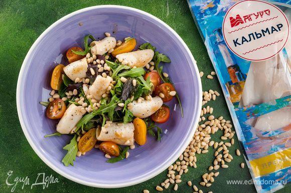 На сервировочное блюдо выложите кальмары, руколу, помидоры. Полейте все второй половиной заправки-маринада и посыпьте кедровыми орешками. Приятного аппетита!