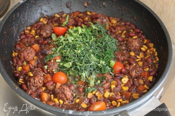 К концу приготовления добавьте зелень, половинки помидорок черри и доведите блюдо до готовности еще пару минут.