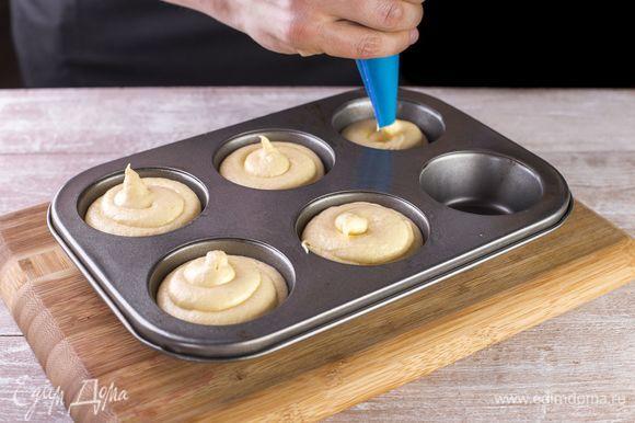 Смажьте формы для маффинов растительным маслом, наполните тестом примерно на три четверти.