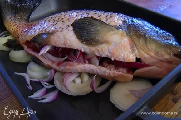 В глубокий тяжелый сотейник с крышкой выложить кольца белого лука, на них поместить карпа, в брюшко рыбы вложить красный лук.