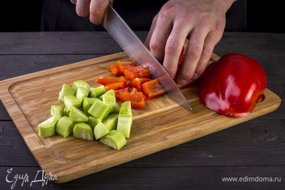 Очистите от семян и перегородок сладкие перцы. Снимите кожуру с огурцов. Нарежьте все ломтиками.