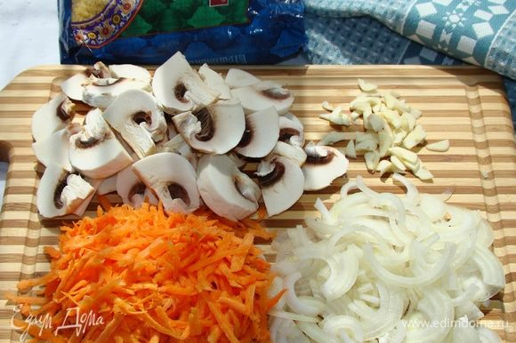 Нашинковать лук соломкой, морковь натереть на крупной терке, чеснок порубить не сильно мелко, грибы нарезать на крупные ломтики. Все обжарить на оливковом масле до золотистого цвета.