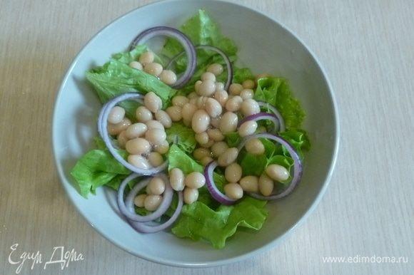 С фасоли ТМ «Фрау Марта» слить жидкость, добавить к салатным листьям. Лук нарезать тонкими кольцами.