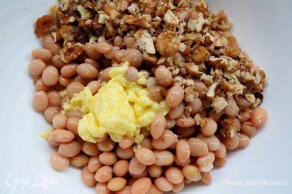 К фасоли добавить растопленное масло, половину рубленых орехов.